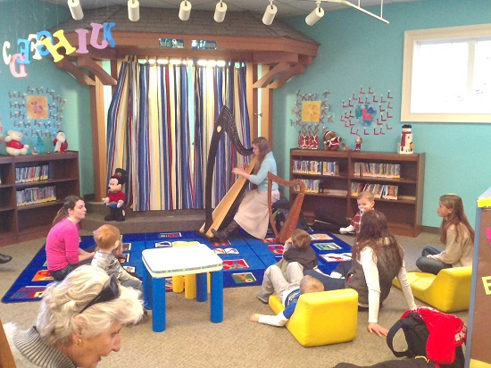 Rachel playing the harp at the children's library day